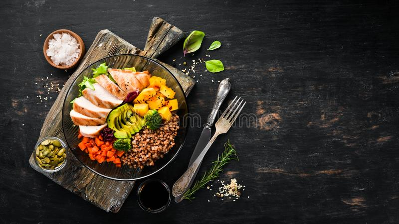 Bowl Buddha. Buckwheat, pumpkin, chicken fillet, avocado, carrots. On a black background. royalty free stock images