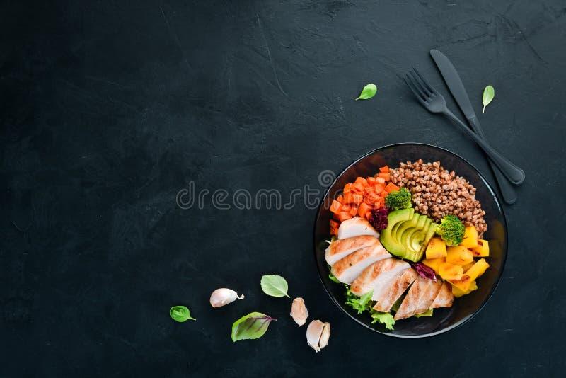Bowl Buddha. Buckwheat, pumpkin, chicken fillet, avocado, carrots. On a black background. stock images