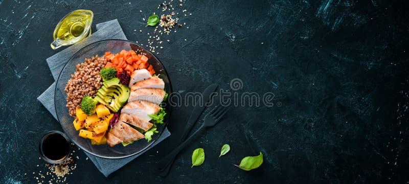 Bowl Buddha. Buckwheat, pumpkin, chicken fillet, avocado, carrots. On a black background. royalty free stock photography