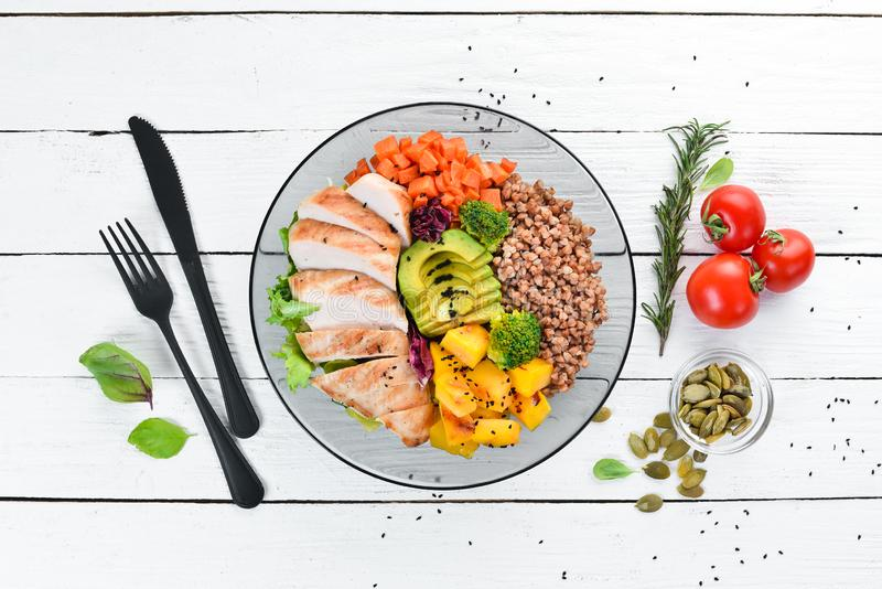 Bowl Buddha. Buckwheat, pumpkin, chicken fillet, avocado, carrots. On a white wooden background. royalty free stock image