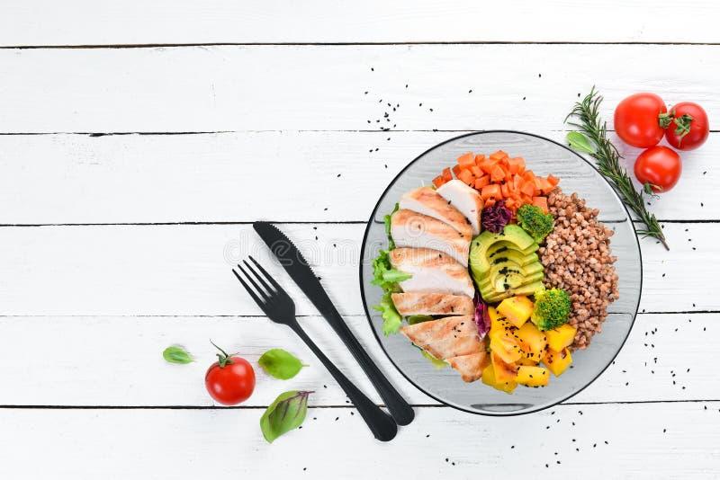 Bowl Buddha. Buckwheat, pumpkin, chicken fillet, avocado, carrots. On a white wooden background. stock image