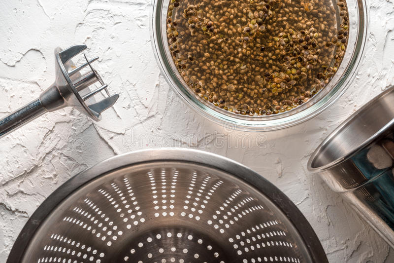 Bowl with cannabis seeds, a blender and a sieve on a white table. Horizontal stock images