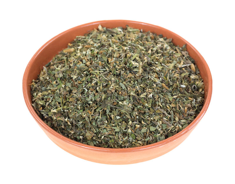 Bowl of catnip. A small bowl filled with catnip herbs on a white background stock image