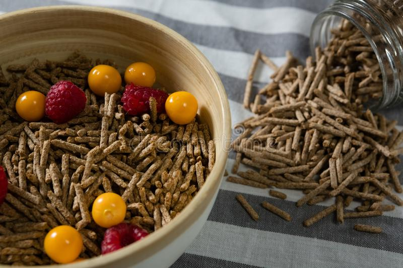 Bowl of cereal bran stick with golden berries and raspberries royalty free stock photo