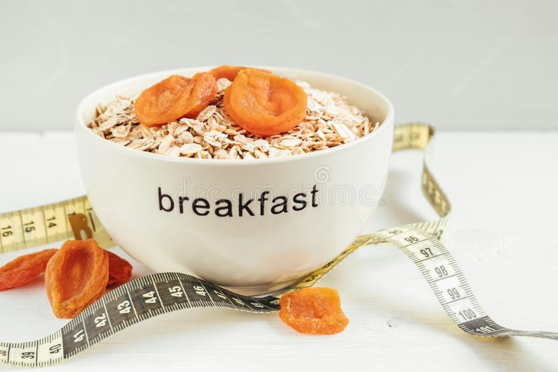 Bowl with cereal flakes, dried apricots and measuring tape. Healthy eating concept royalty free stock photography