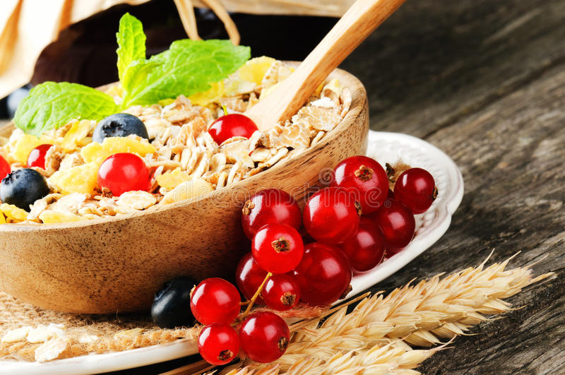 Bowl with cereals and fresh berries. On wooden table stock image