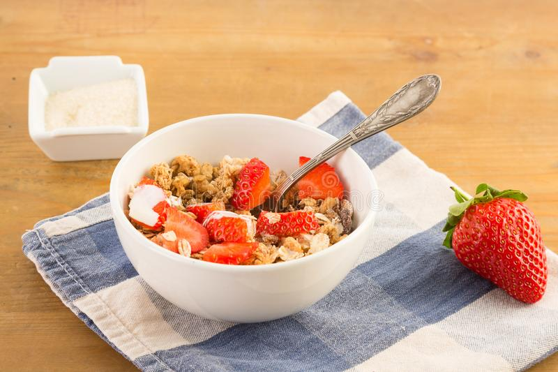 Bowl of cereals with strawberries resting on a blue napkin. On a wooden table stock photography