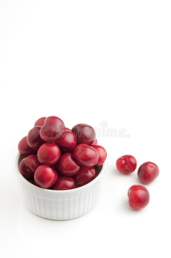 Bowl of Cherries. Fresh picked cherries in a white bowl on white background stock image