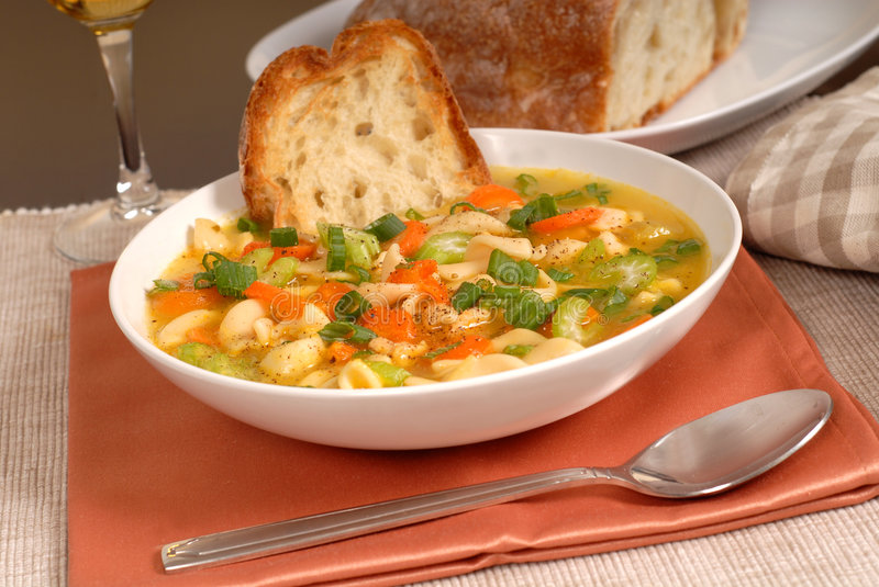 Bowl of chicken noodle soup with rustic bread and a glass of win royalty free stock image