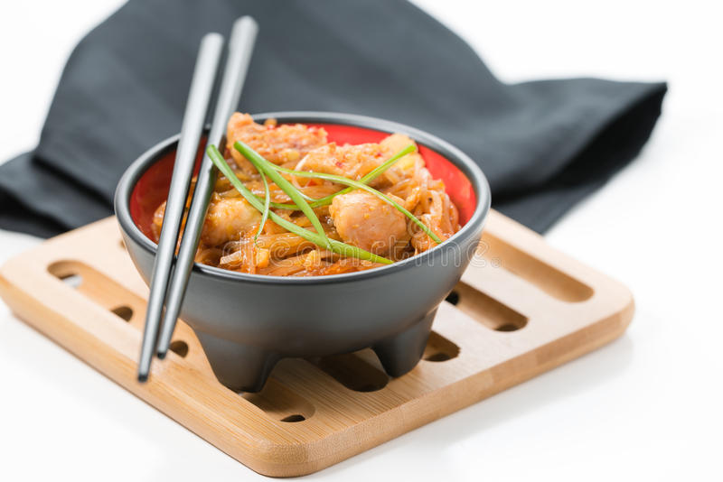 Bowl of Chicken Pad Thai. Bowl of delicious chicken pad thai on a bamboo trivet royalty free stock photography