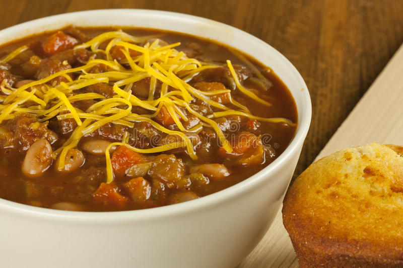 Bowl of Chili with Cornbread. A bowl of chili with cheese on top and some cornbread on the side stock photo