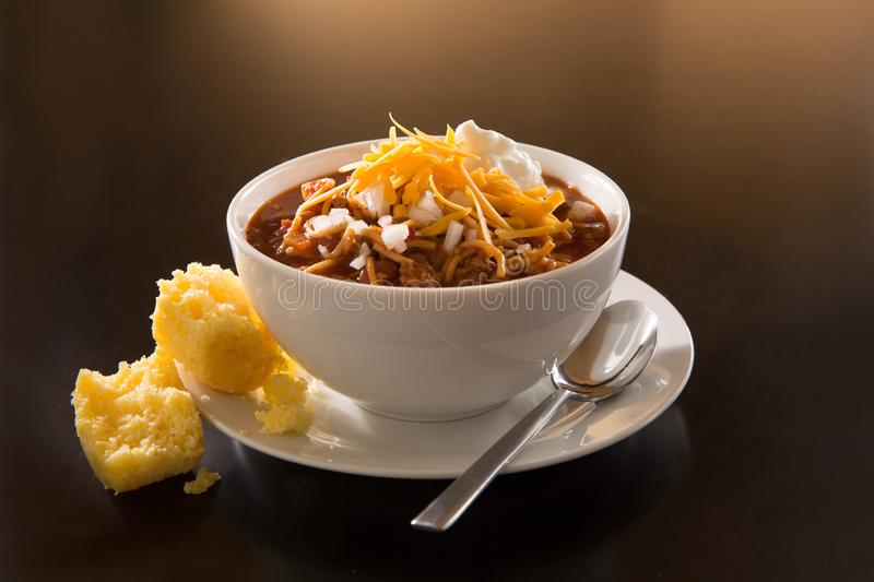Bowl of chili with corn muffin. Bowl of chili with onions, shredded cheese, greek yogurt and a corn muffin in white dishes stock photo