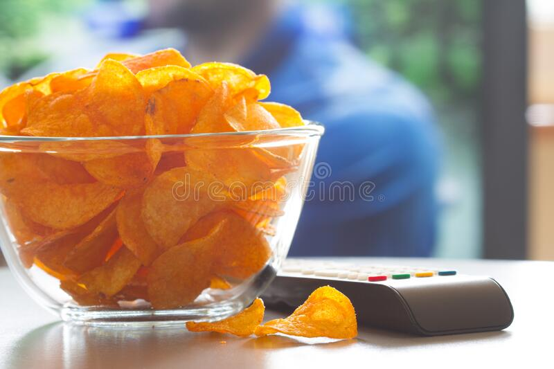 Bowl of chips, remote control and background television. Home cinema concept stock photography
