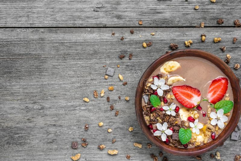 Bowl of choclate and banana smoothie with chocolate granola, strawberry and pomegranate seeds decorated with flowers. Top view with copy space. healthy stock photos