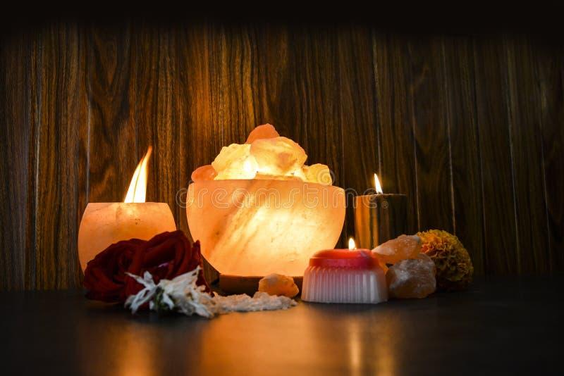 Bowl Chunks Lamps & Natural Salt Candle Holder | Himalayan Salt. Bowl Chunks Lamps & Natural Salt Candle Holder with wooden & black background. Natural salt stock image