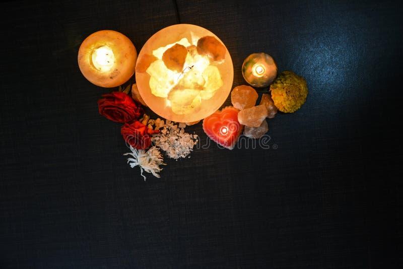 Bowl Chunks Lamps & Natural Salt Candle Holder | Himalayan Salt. Bowl Chunks Lamps & Natural Salt Candle Holder with wooden & black background. Natural salt royalty free stock image