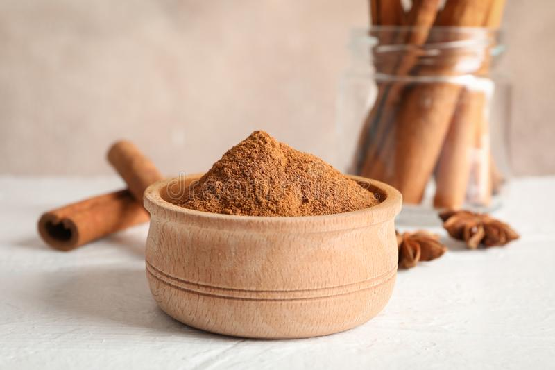 Bowl with cinnamon powder, cinnamon sticks and anise on white background royalty free stock photos