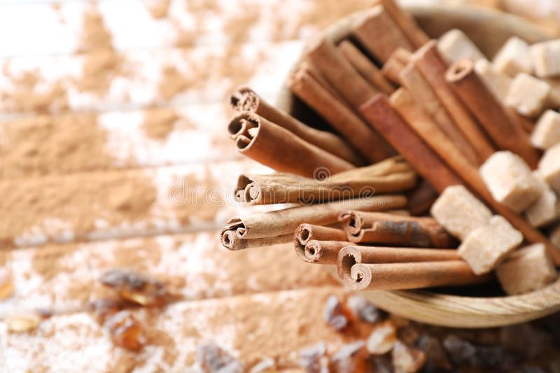 Bowl with cinnamon sticks and sugar on wooden background, closeup royalty free stock images