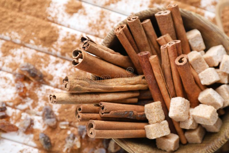 Bowl with cinnamon sticks and sugar on wooden background, closeup stock photos
