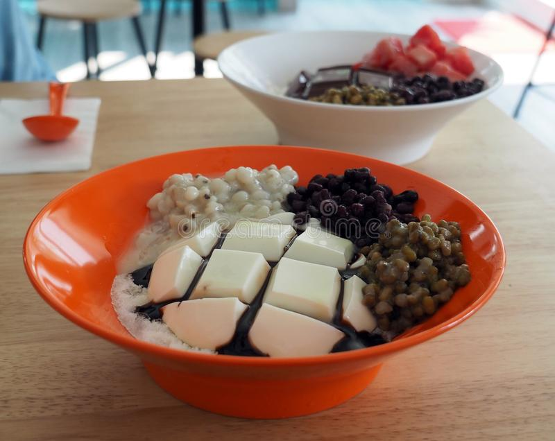 Bowl of cold tofu pudding with red bean, mung bean and millet on top with chocolate sauce and milk on shaved ice. royalty free stock image