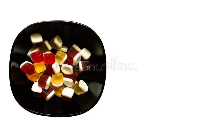 Bowl of colorful cube shaped jelly candies on white background with copy space royalty free stock photography