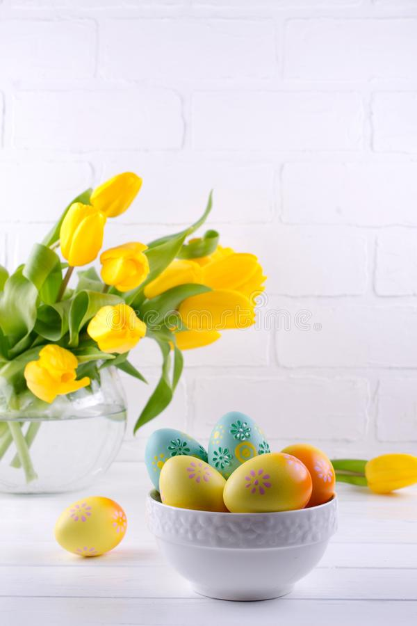 Bowl with colorful Easter eggs, spring easter decoration on white wooden table with bouquet of yellow tulip flowers in glass vase royalty free stock images