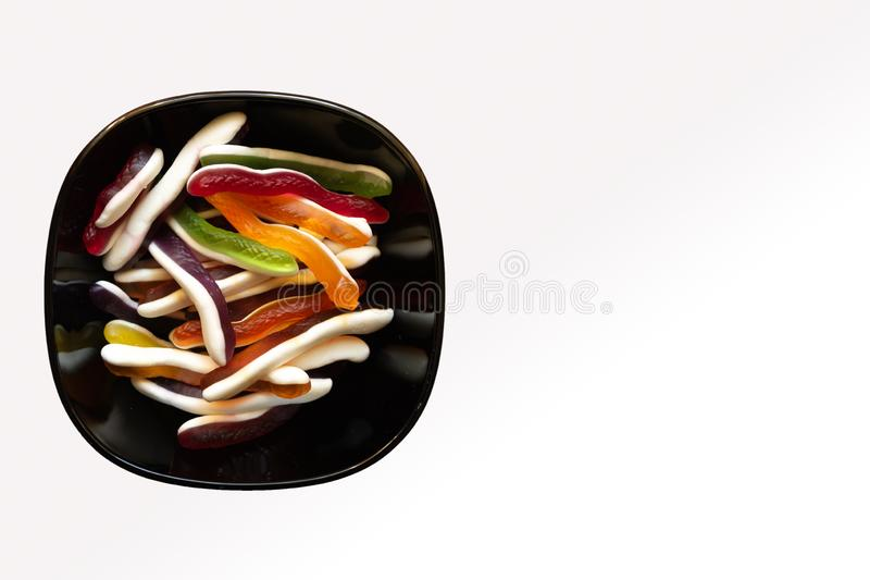 Bowl of colorful snake shaped jelly candies on white background with copy space stock photography