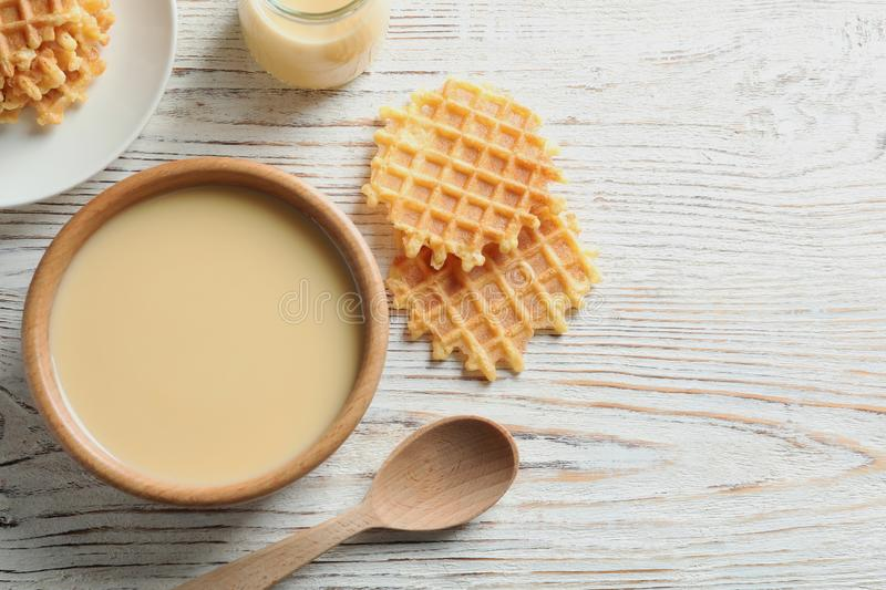 Bowl of condensed milk and waffles served on wooden table, top view with space for text. Dairy products stock photography