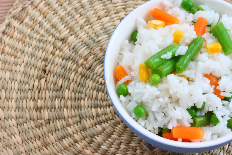 Bowl with cooked rice with mixed vegetable. Close up view of cooked rice in bowl - with mixed of colorful vegetable on natural background stock image