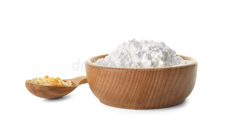 Bowl of corn starch and spoon with kernels. On white background royalty free stock photo