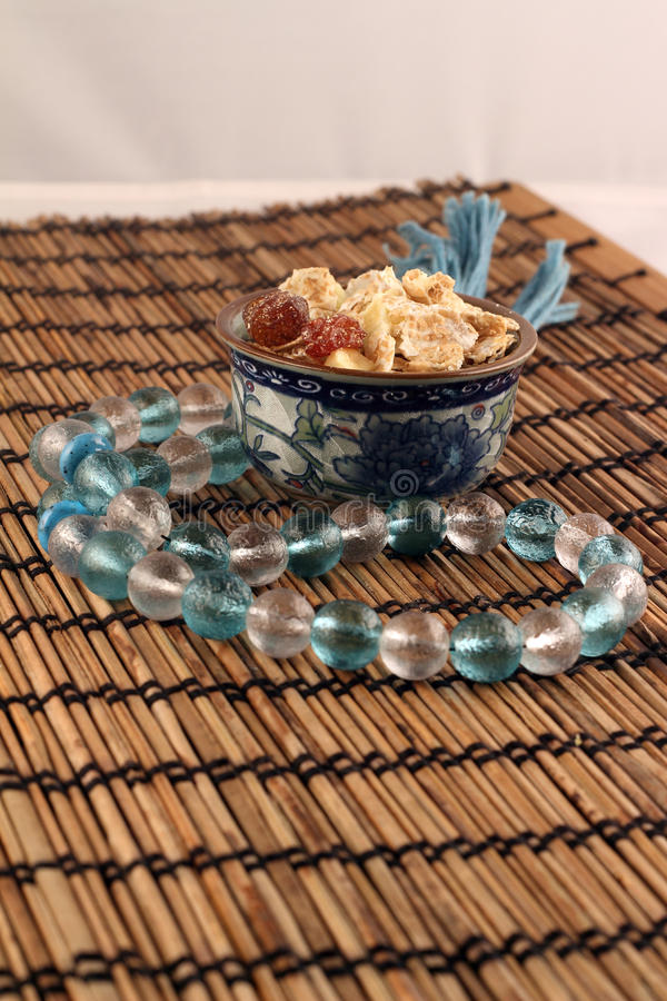 A bowl of cornflakes and string of beads stock image