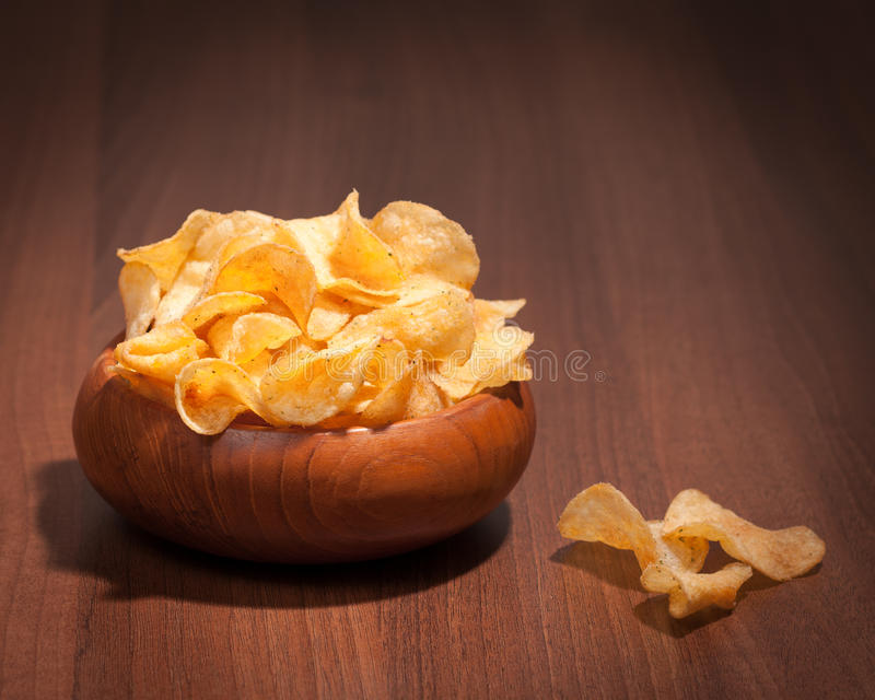 Bowl Of Crisps. Flavoured potato crisps in wooden bowl on table stock photos