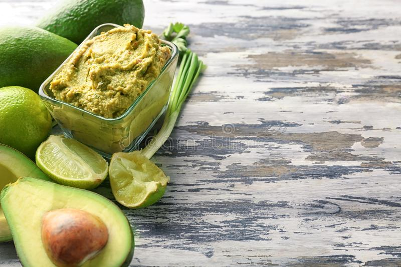 Bowl with delicious guacamole, ripe avocados and lime on table royalty free stock photo