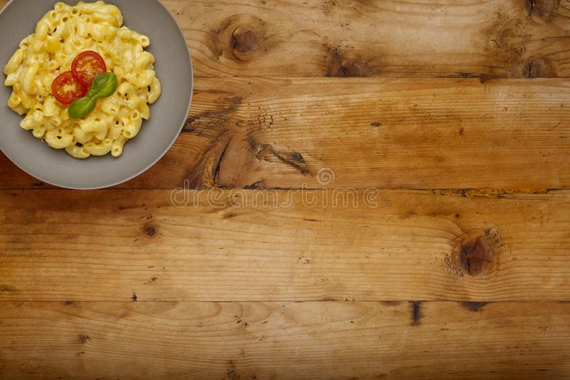 A bowl of delicious Macaroni and cheese, topped with cherry tomatoes and basil, on a wooden background with copy space royalty free stock photography