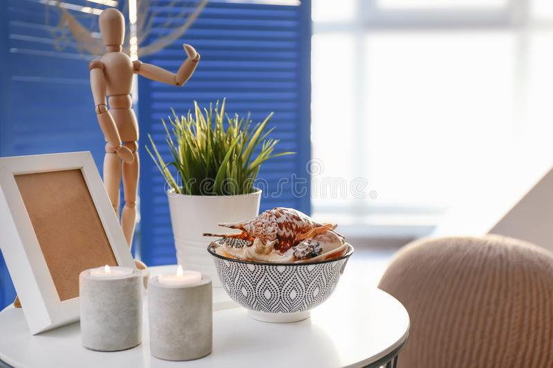 Bowl with different sea shells and burning candles on white table royalty free stock images