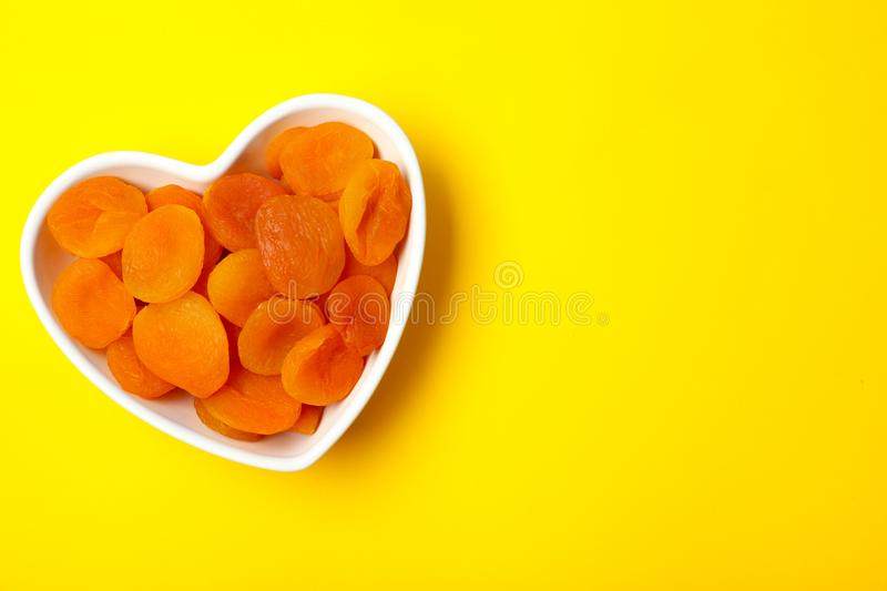 Bowl of dried apricots on color background, top view with space for text. stock image