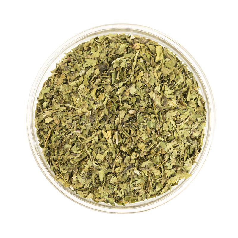 Bowl of Dried Cilantro Leaves Isolated. Glass bowl full of dried cilantro leaves, isolated on white and viewed from directly above stock photo