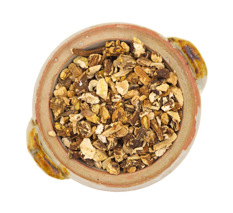 Bowl of dried dandelion root. Top view of a bowl filled with dried dandelion root on a white background royalty free stock photography