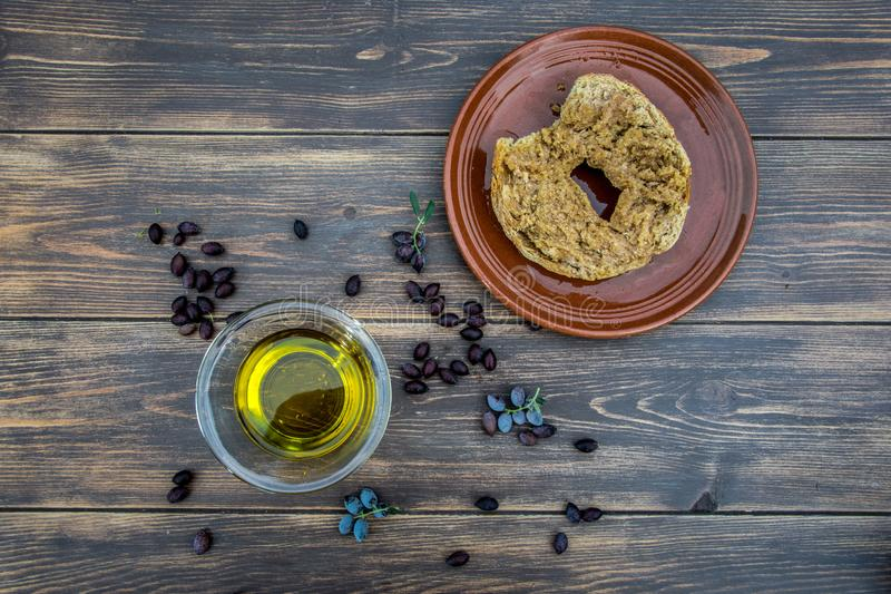 Bowl with extra virgin olive oil, olives, a fresh branch of olive tree and cretan rusk dakos close up on wooden table, Crete, Gree royalty free stock photography