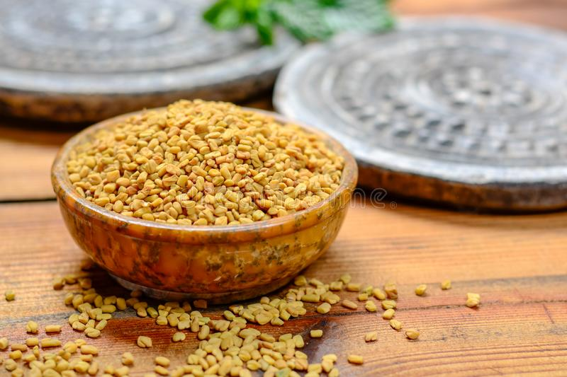 Bowl with fenugreek seeds close up, used for cooking and traditinal medicine, spices collection royalty free stock image