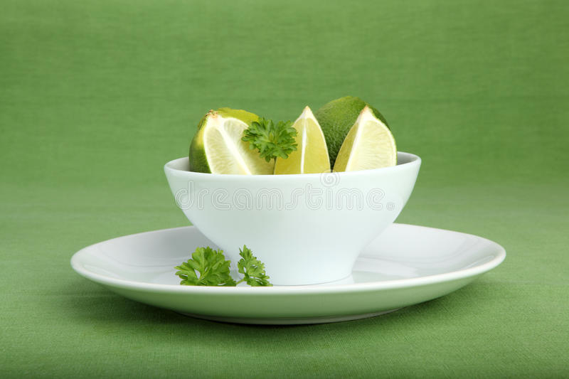 Bowl filled with limes and parsley on green background.  stock photos