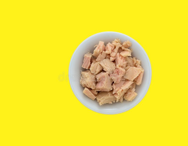 Bowl filled with solid white albacore tuna on a yellow background royalty free stock photography