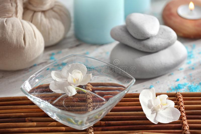 Bowl with floating flower in water on table royalty free stock images