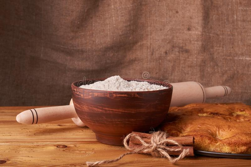 A bowl with flour and apricot cake on a wooden background stock image