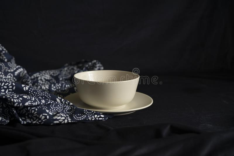 A bowl on the flower cloth in black background.  stock image