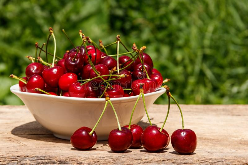 Bowl with fresh cherry on rustic wooden table outdoor. Bowl with fresh cherry on the rustic wooden table outdoor stock image