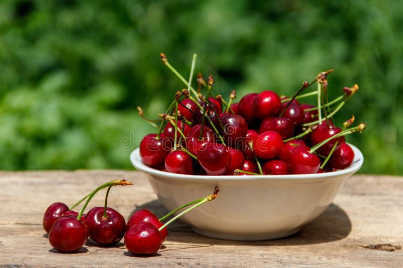 Bowl with fresh cherry on rustic wooden table outdoor. Bowl with fresh cherry on a rustic wooden table outdoor royalty free stock photography