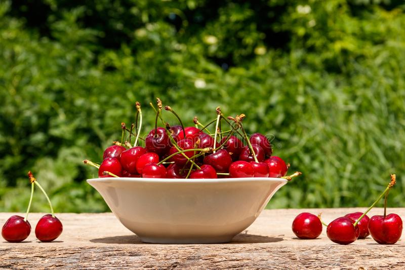 Bowl with fresh cherry on rustic wooden table outdoor. Bowl with fresh cherry on a rustic wooden table outdoor royalty free stock photos