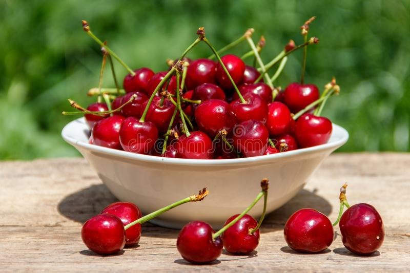 Bowl with fresh cherry on rustic wooden table outdoor. Bowl with fresh cherry on a rustic wooden table outdoor stock photography