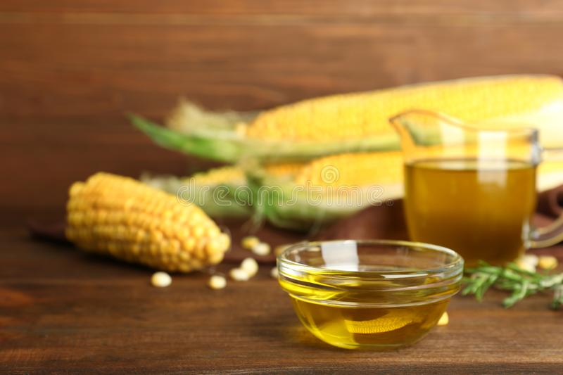 Bowl with fresh corn oil on table. Bowl with fresh corn oil on wooden table royalty free stock photography